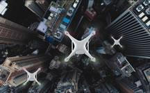 Drones fly above a city