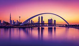 Gorgeous Dubai Water Canal and footbridges basked in purple, pink and orange sunset